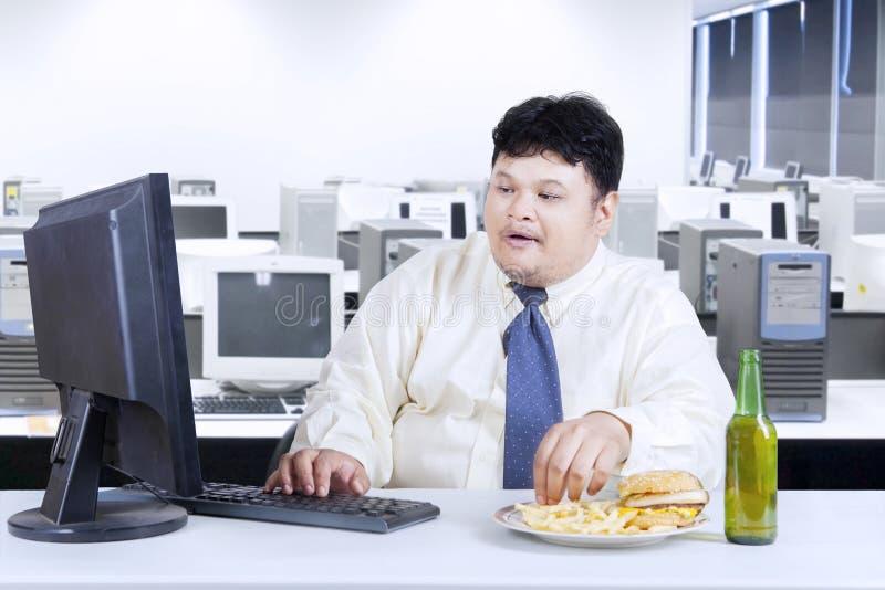 Hombre de negocios de la obesidad que trabaja en oficina imágenes de archivo libres de regalías