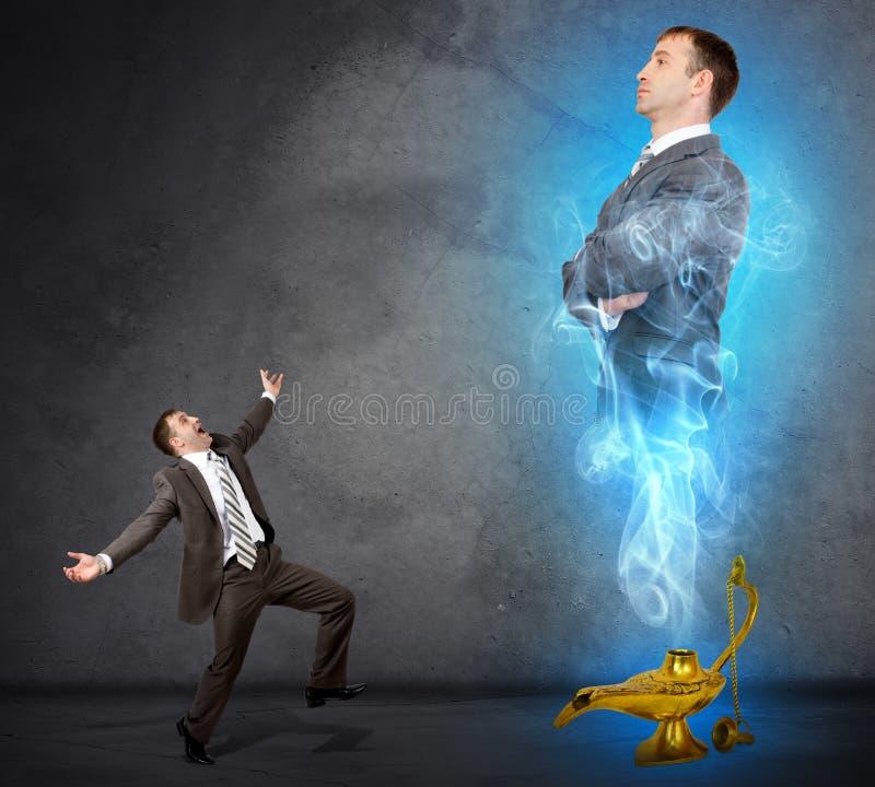 Hombre de negocios de los genios que aparece de la lámpara mágica imagenes de archivo