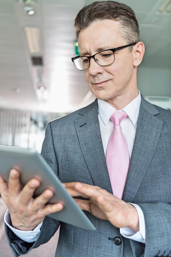 Hombre de negocios de mediana edad usando la tableta en oficina imagen de archivo libre de regalías