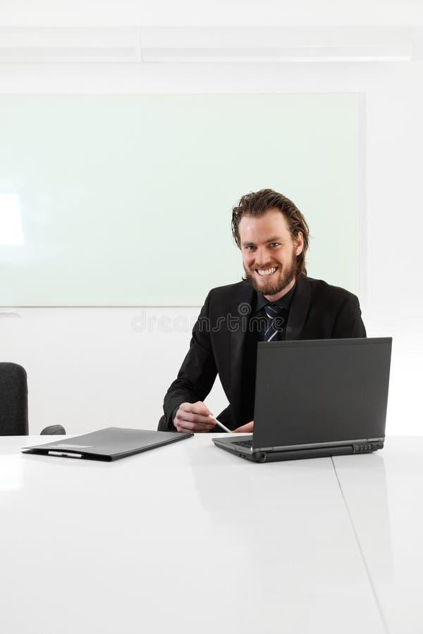 Hombre de negocios de pelo largo que se sienta en una sala de juntas imagen de archivo