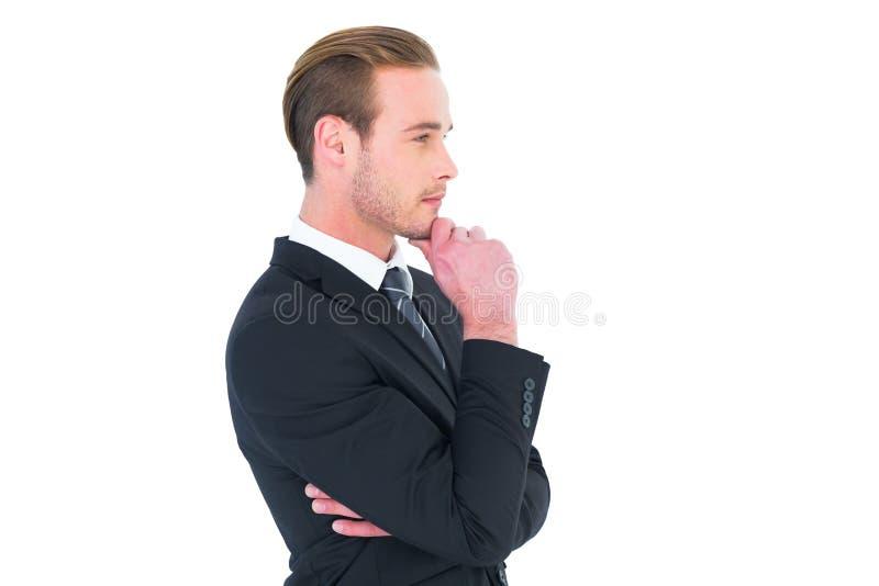 Hombre de negocios de pensamiento que se coloca con la mano en la barbilla fotografía de archivo libre de regalías
