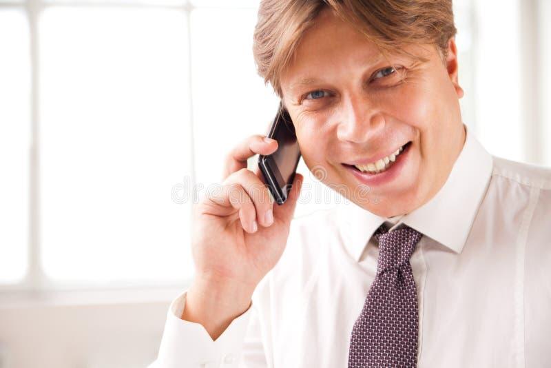 Hombre de negocios de risa en el teléfono en su oficina fotografía de archivo libre de regalías
