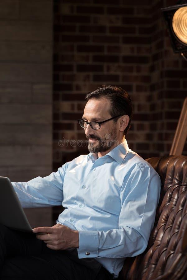 Hombre de negocios de trabajo duro alegre que se sienta en el ordenador portátil imágenes de archivo libres de regalías