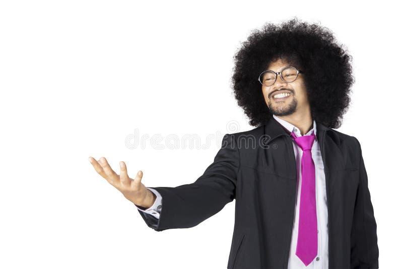 Hombre de negocios del Afro que lleva a cabo algo en su mano fotos de archivo libres de regalías