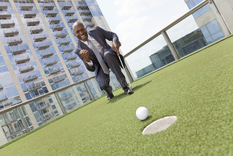 Hombre de negocios del afroamericano que juega a golf del tejado imagenes de archivo