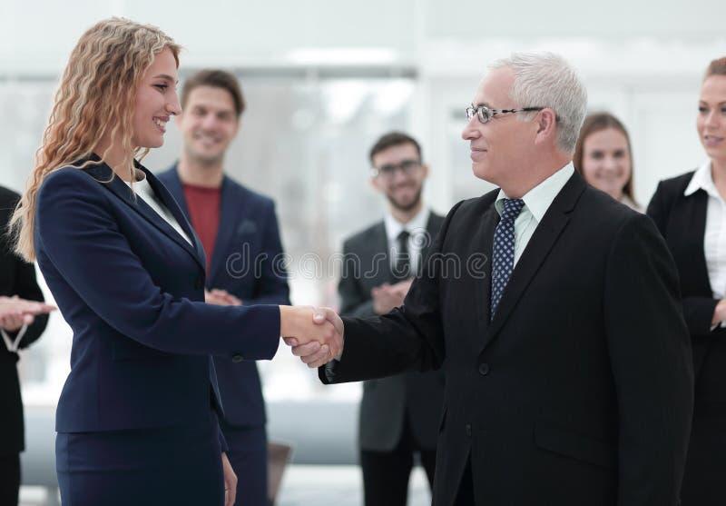 Hombre de negocios del apretón de manos y mujer de negocios serios foto de archivo libre de regalías
