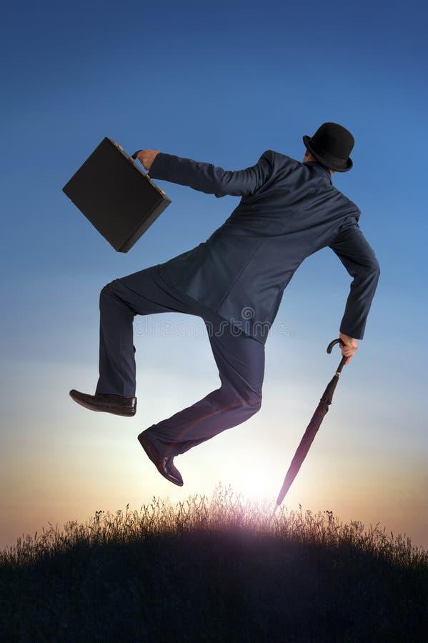 Hombre de negocios del concepto del éxito empresarial que golpea los talones con el pie en aire imagenes de archivo