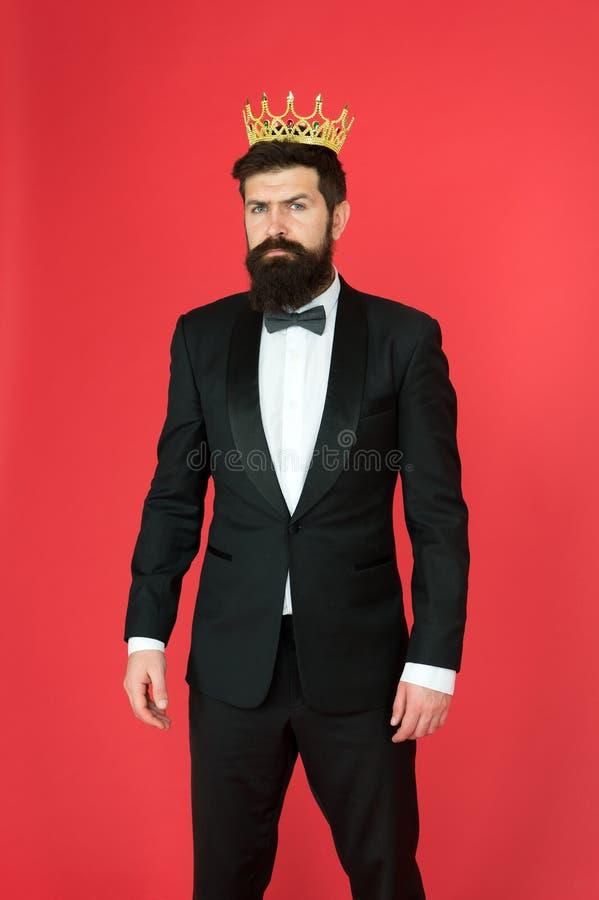 Hombre de negocios del egoísta en smoking y corona adaptados Egoísta barbudo del hombre en smoking y corbata de lazo Protuberanci fotos de archivo