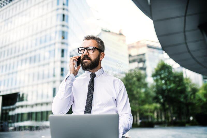 Hombre de negocios del inconformista con el ordenador portátil y smartphone en la ciudad fotos de archivo