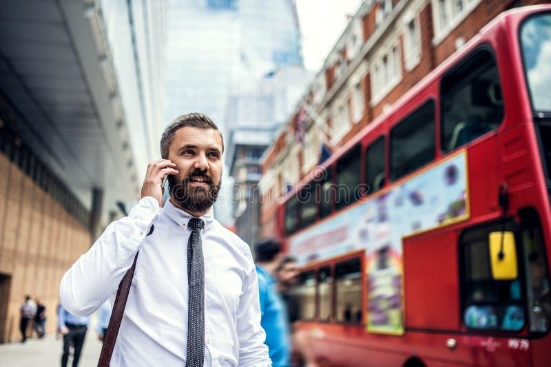 Hombre de negocios del inconformista en la calle en Londres, haciendo una llamada de teléfono fotos de archivo libres de regalías