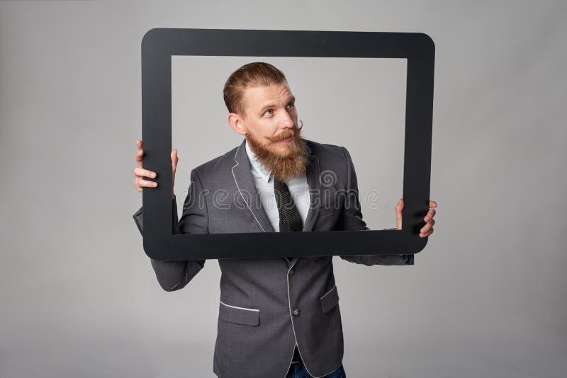 Hombre de negocios del inconformista que mira furtivamente fuera de marco fotografía de archivo libre de regalías