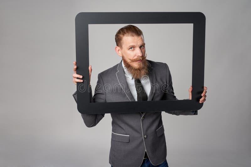 Hombre de negocios del inconformista que mira furtivamente fuera de marco imagen de archivo