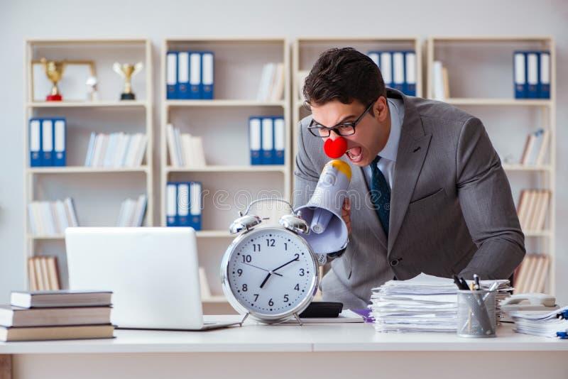 Hombre de negocios del payaso en el enojado de la oficina frustrado con el megáfono fotografía de archivo libre de regalías