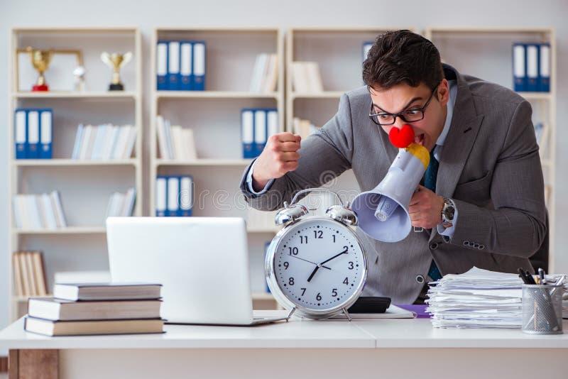 Hombre de negocios del payaso en el enojado de la oficina frustrado con el megáfono foto de archivo