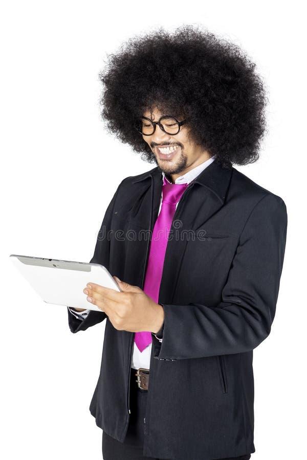 Hombre de negocios del pelo rizado que usa una tableta en estudio imagen de archivo libre de regalías