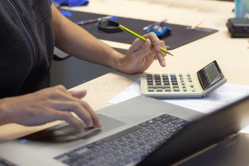 Hombre de negocios del primer que usa la calculadora y el ordenador portátil del conmputer para c imagen de archivo libre de regalías