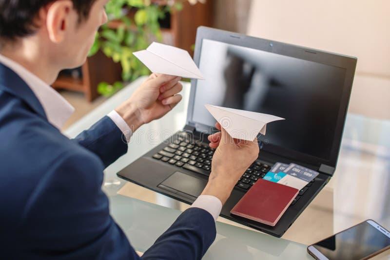 Hombre de negocios del hombre que sostiene papiroflexia de un aeroplano de papel en sus manos Concepto de compra y de reservación fotografía de archivo
