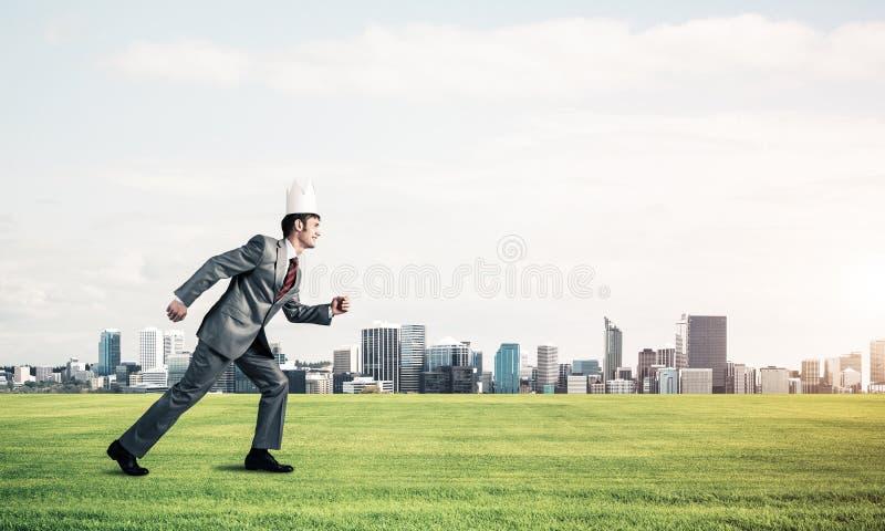 Hombre de negocios del rey en el traje elegante que corre en hierba verde y paisaje urbano moderno en el fondo fotografía de archivo