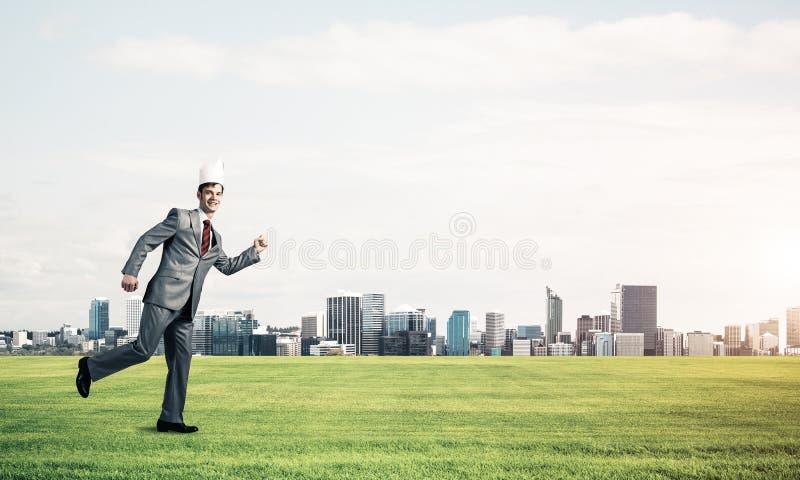 Hombre de negocios del rey en el traje elegante que corre en hierba verde y paisaje urbano moderno en el fondo imagenes de archivo