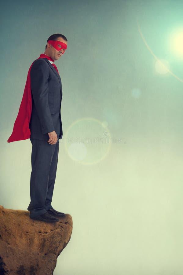 Hombre de negocios del super héroe en un precipicio fotos de archivo
