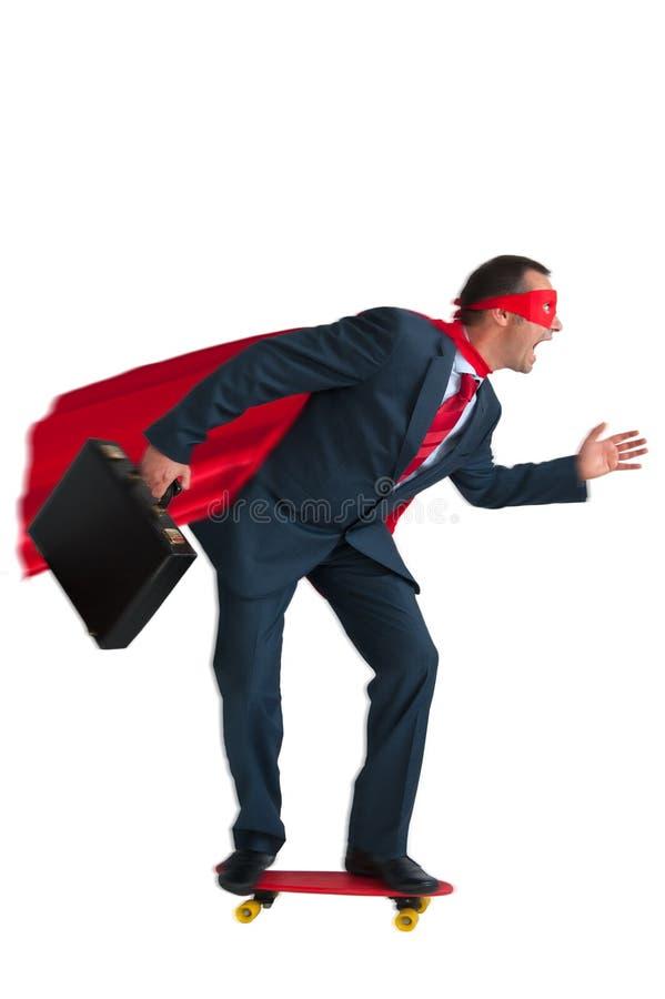 Hombre de negocios del super héroe que monta un monopatín imagenes de archivo