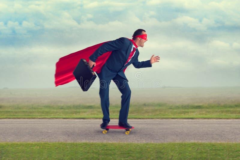 Hombre de negocios del super héroe que monta un monopatín fotografía de archivo