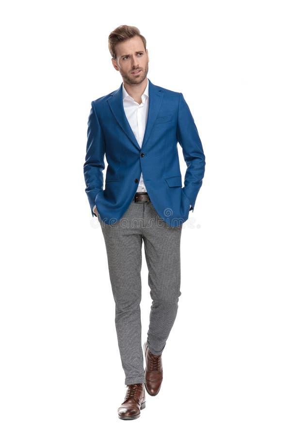 Hombre de negocios del trastorno que camina adelante con ambas manos en sus bolsillos imagen de archivo