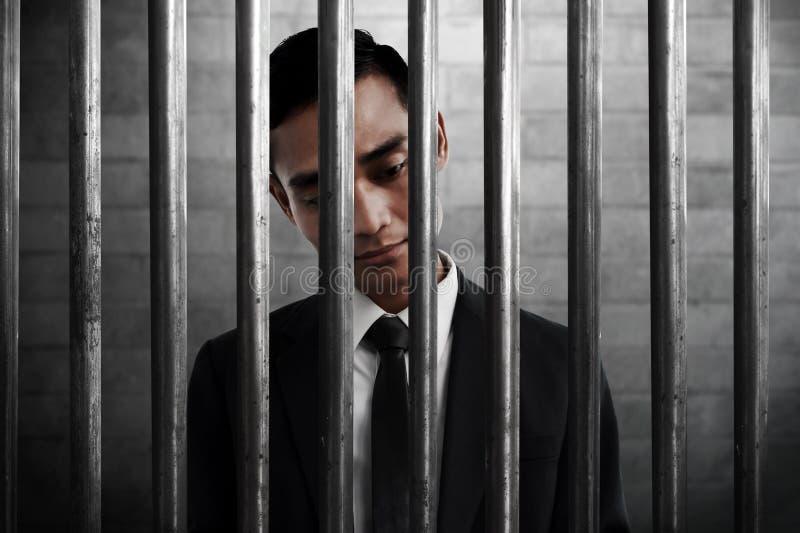 Hombre de negocios dentro de la prisión con la expresión triste imagenes de archivo