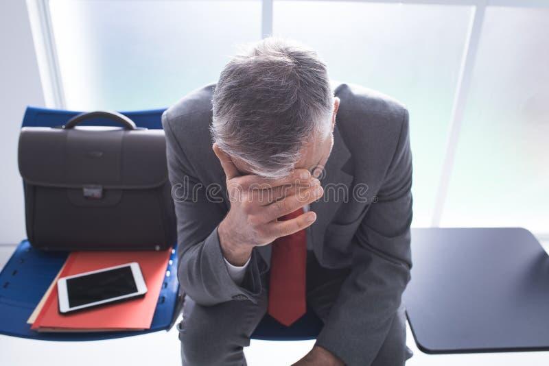 Hombre de negocios deprimido en la sala de espera imagen de archivo libre de regalías