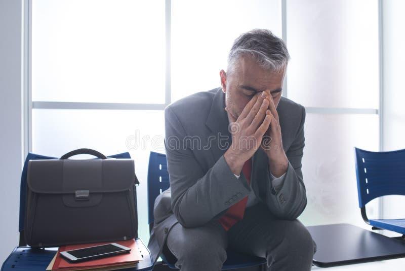 Hombre de negocios deprimido en la sala de espera foto de archivo libre de regalías