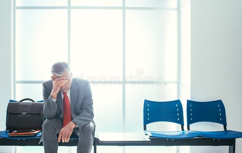 Hombre de negocios deprimido en la sala de espera imágenes de archivo libres de regalías