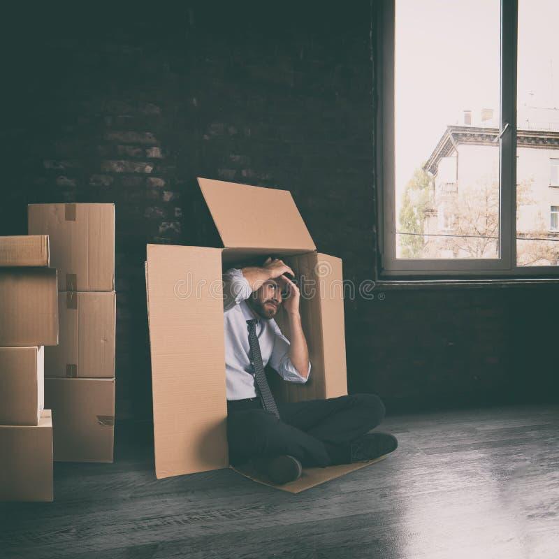 Hombre de negocios deprimido para el fracaso de la compa??a ocultada en una caja de cart?n foto de archivo libre de regalías