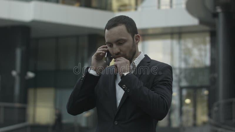 Hombre de negocios descontentado que habla seriamente por el teléfono, derecho fuera de la oficina fotos de archivo