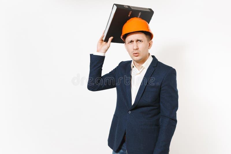 Hombre de negocios descontento Concerned en el traje oscuro, casco de protección protector que sostiene la carpeta negra para el  imágenes de archivo libres de regalías