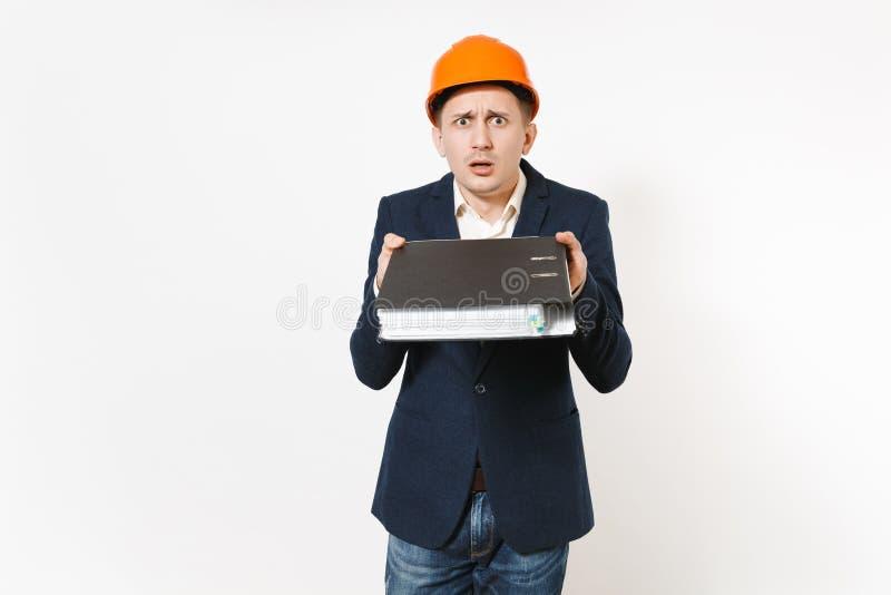 Hombre de negocios descontento Concerned en el traje oscuro, casco protector de la construcción que sostiene la carpeta negra par imagen de archivo libre de regalías