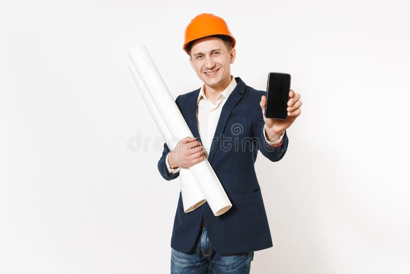 Hombre de negocios descontento joven en el traje oscuro, el casco de protección protector sosteniendo planes de los modelos y el  imagen de archivo libre de regalías