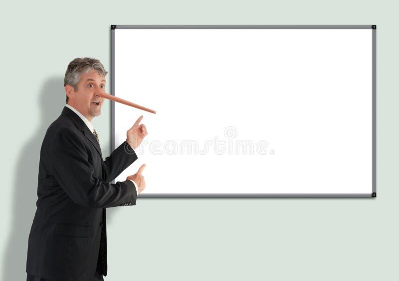 Hombre de negocios deshonesto de mentira con el crecimiento de la nariz de Pinocchio que señala para esconder al tablero blanco foto de archivo