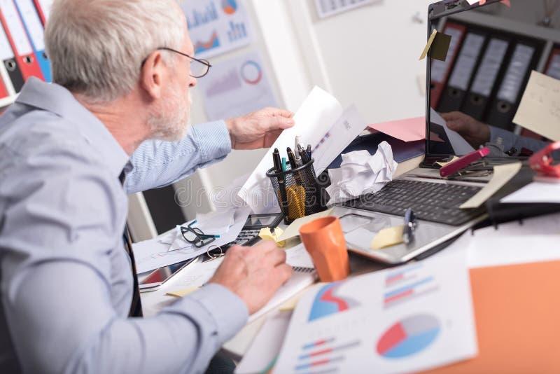 Hombre de negocios desorganizado que busca documentos fotos de archivo