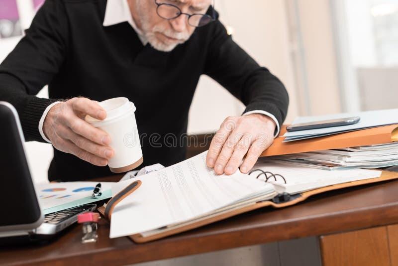 Hombre de negocios desorganizado que busca documentos imagen de archivo libre de regalías