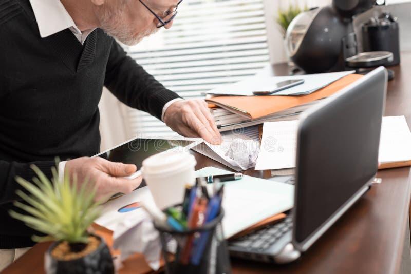 Hombre de negocios desorganizado que busca documentos foto de archivo libre de regalías