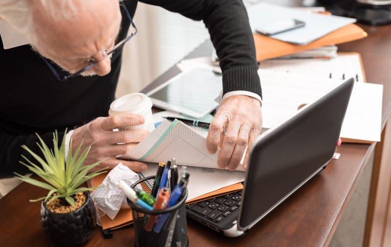 Hombre de negocios desorganizado que busca documentos fotos de archivo libres de regalías