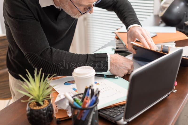 Hombre de negocios desorganizado que busca documentos imagen de archivo