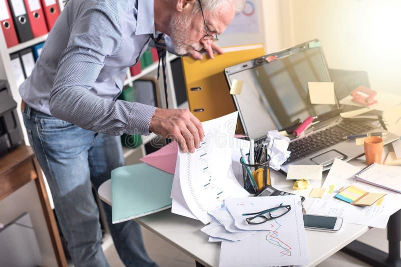 Hombre de negocios desorganizado que busca los documentos, efecto luminoso imágenes de archivo libres de regalías