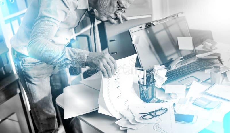 Hombre de negocios desorganizado que busca los documentos, efecto luminoso imagenes de archivo