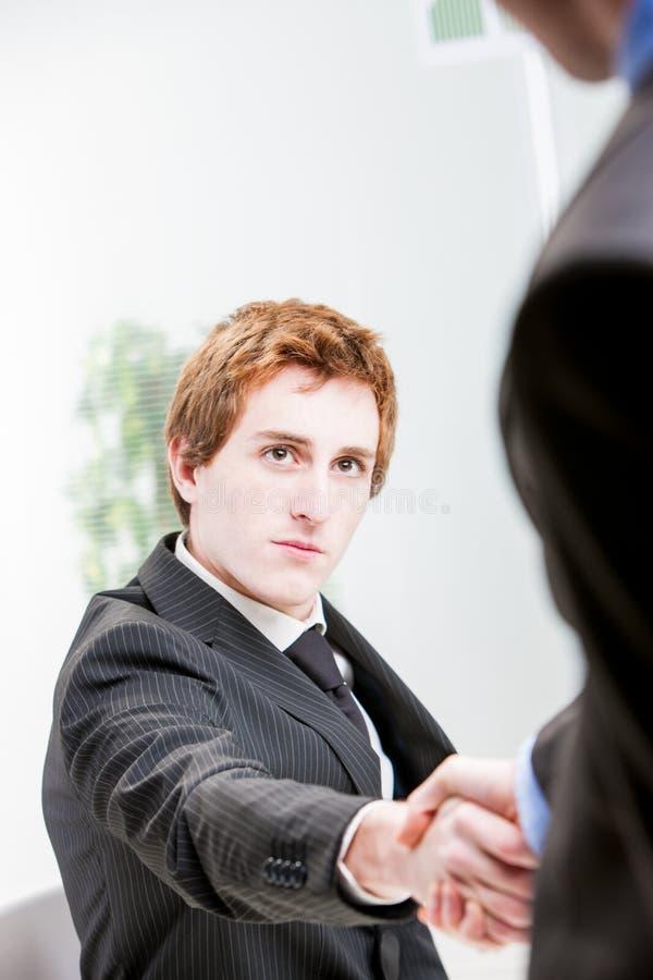 Hombre de negocios dirigido rojo que sacude las manos imagen de archivo libre de regalías