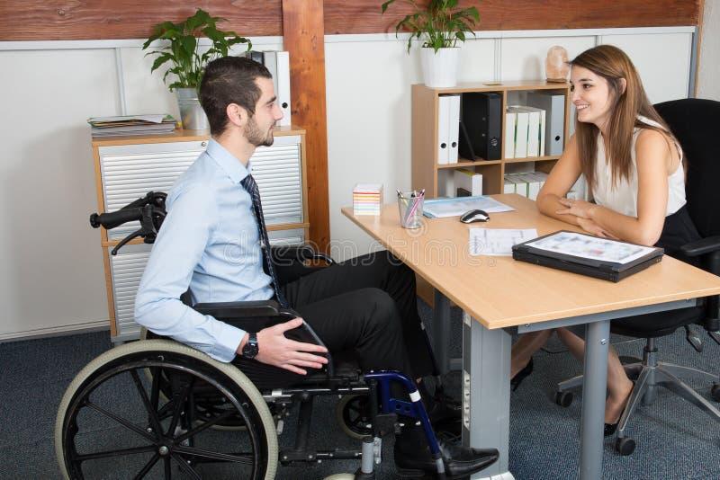 Hombre de negocios discapacitado hermoso en una silla de ruedas en su oficina delante de una mujer joven hermosa imagen de archivo