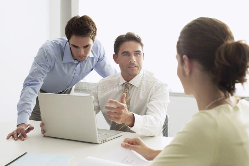 Hombre de negocios Discussing With Colleagues en el escritorio imagen de archivo libre de regalías