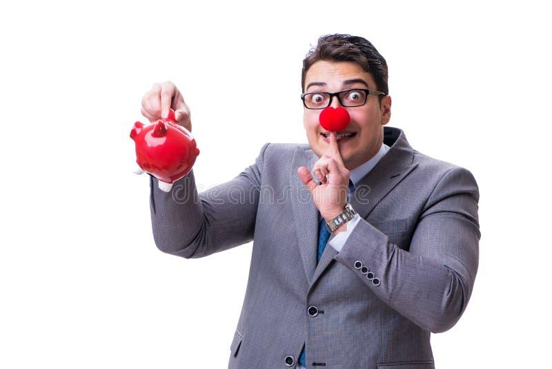 Hombre de negocios divertido con la nariz roja que sostiene una hucha aislada encendido imagenes de archivo