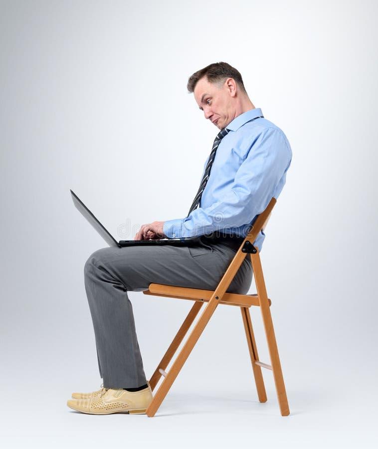 Hombre de negocios divertido con un ordenador portátil que se sienta en una silla en fondo imágenes de archivo libres de regalías
