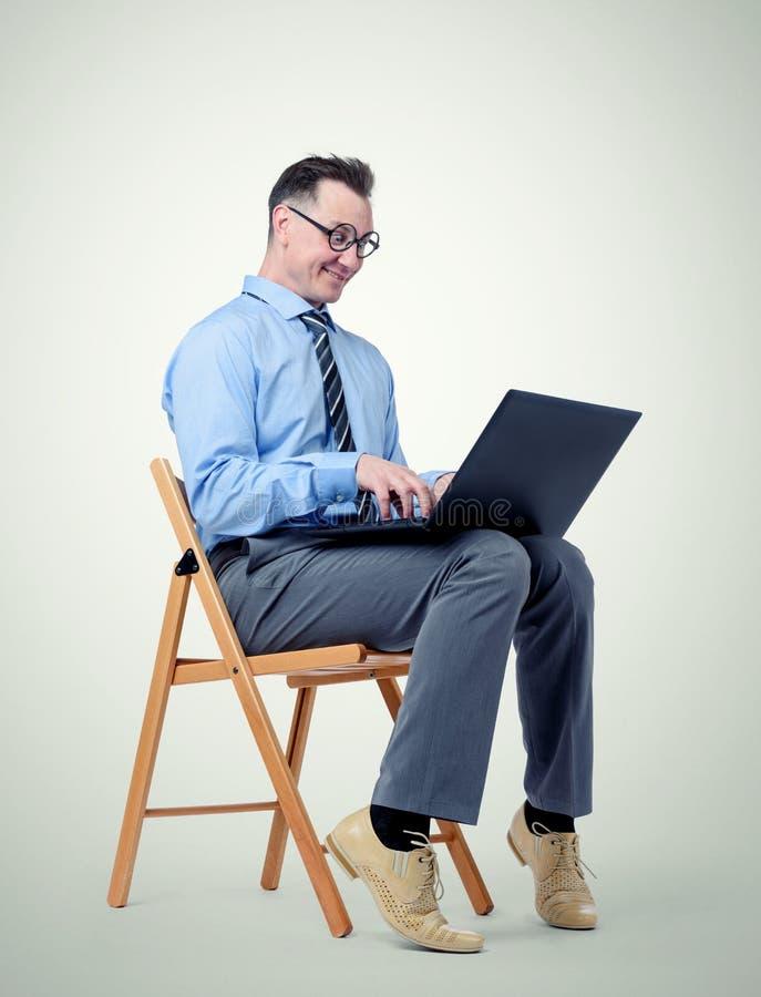 Hombre de negocios divertido con un ordenador portátil que se sienta en una silla en fondo foto de archivo